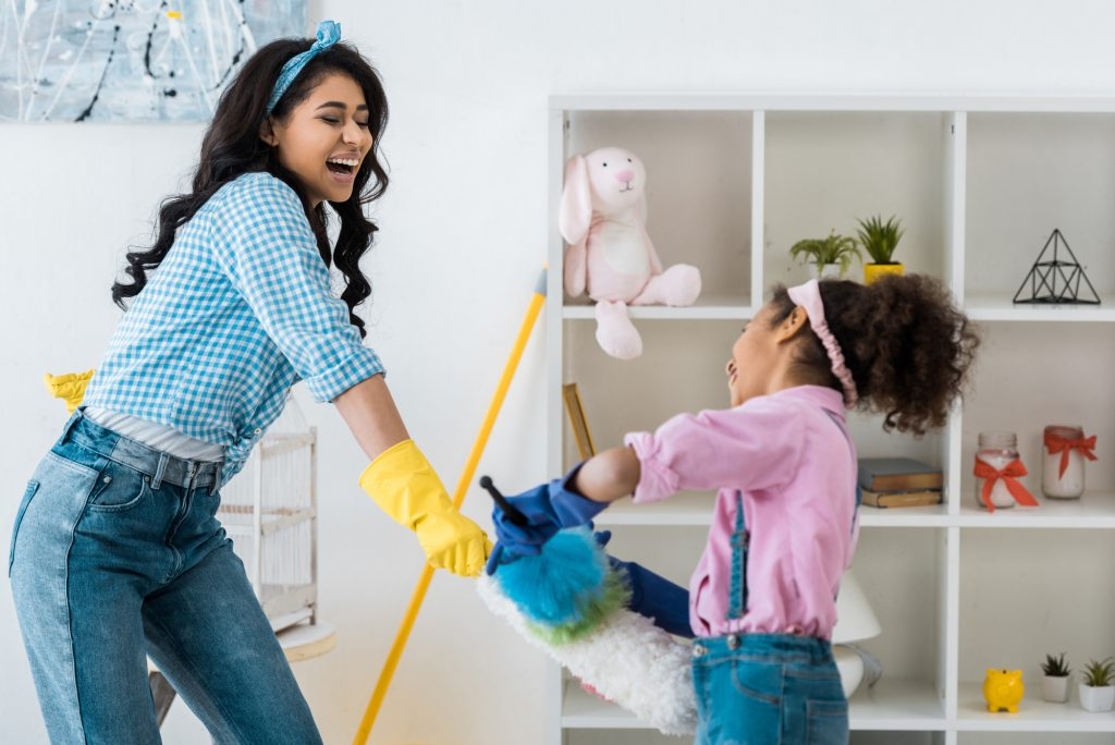 Laughing african american mother with cute daughter having fun while fighting with dusters