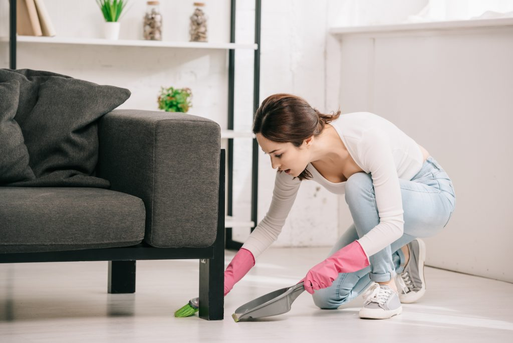 Young housewife sweeping floor near sofa with brush and scoop
