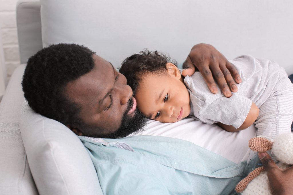 African-American man with his cute baby lying on sofa