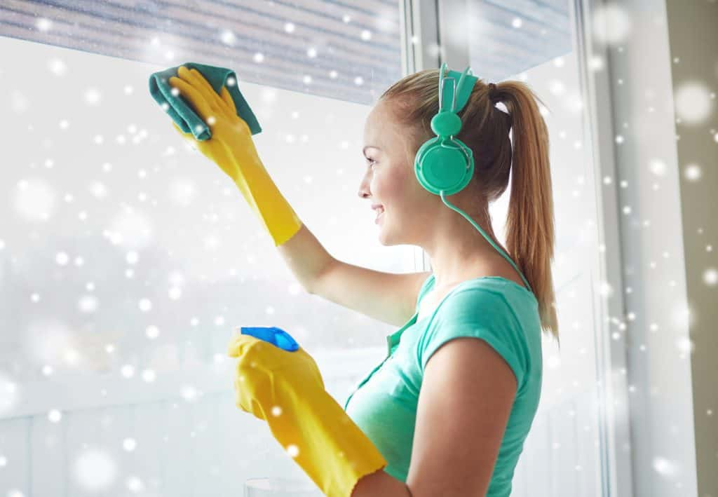 Happy woman with headphones cleaning window